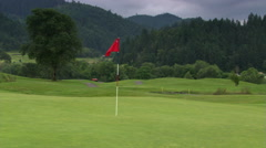 Red flag waving above hole on hilly golf  course Stock Footage
