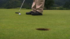 Putter tapping ball, which rolls into hole in foreground Stock Footage