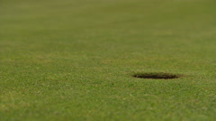 Golf ball rolling from left to drop into close-up hole at right; hand retrieves Stock Footage