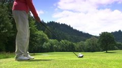 Golfer addressing ball, swinging club, and watching ball sail down the fairway Stock Footage