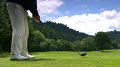 Golfer swinging, airborne ball angling slightly left - stock footage