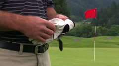 Golfer adjusting glove, taking putter, and walking out of frame at left Stock Footage