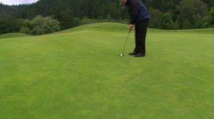 Golfer putting, zoom-out to hole and ball dropping in Stock Footage