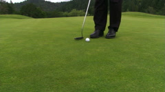Golfer putting, right pan to hole and ball stopping at edge without dropping in - stock footage