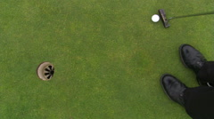 Golfer nudging ball with putter before sinking putt and retrieving ball from cup - stock footage