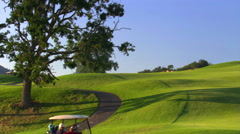 Golfers in carts driving along meandering path over hilly course Stock Footage
