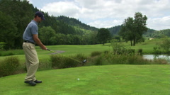Golfer hitting ball over water hazard and down the fairway, tee remaining - stock footage