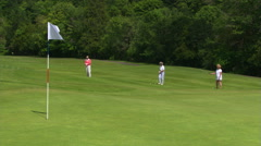 Woman golfer in mid-frame hits toward foreground flag, just missing hole; a Stock Footage