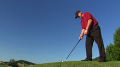 Golfer skylined on hilltop, swing spraying sand and turf toward camera - stock footage