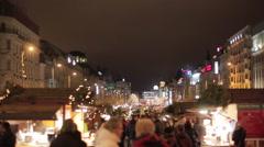Christmas market fair in Prague street with pedestrians walking at night Stock Footage