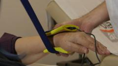 Physiotherapist puts device for electrotherapy massage on injured hand of woman. Stock Footage