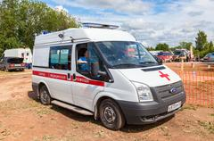 "Ambulance car parked up in the rural street. Text on russian: ""Acute care"" Stock Photos"