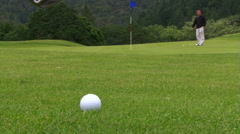 Close to camera, club head hits ball toward flag in center frame, missing hole Stock Footage