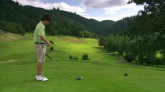 Young golfer adjusting glove and teeing off; watches shot before picking up tee Stock Footage