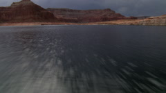 Low, fast flight over Lake Powell under stormy sky - stock footage