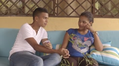 Young latino boy holding his girlfriend's hand while talking on the couch (4k) Stock Footage