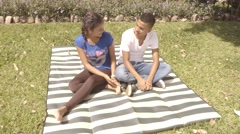 Latin American young couple sits on blanket in lawn talking(4k) Stock Footage