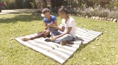 Latin American girl receives a flower from her boyfriend on blanket in lawn (4k) Stock Footage