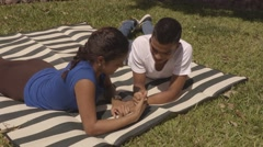 Young latino couple lies on a blanket and has a thumb war (4k) Stock Footage