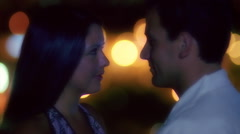 Close-up profiles of romantic couple against a background of soft-focus lights - stock footage