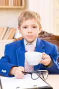 Little boy upholding cup and grabbing glasses - stock photo