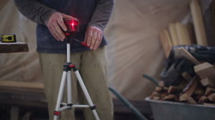 Carpenter working with a construction laser level Stock Footage