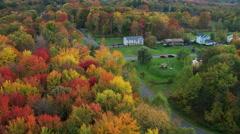 Flying over rural New England neighborhood among autumn woods - stock footage