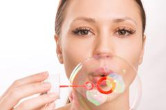 Young girl blowing out a soup bubble Stock Photos