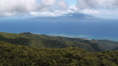 Flying over wooded hilltops on Molokai with Maui in distance. Shot in 2010. Stock Footage