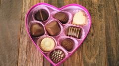 Chocolates in heart shaped box on rustic wood table. Stock Footage