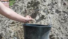 Collect concrete with a shovel in a bucket. the sand is loaded into the bucket a Stock Footage