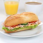 Healthy eating sub sandwich baguette for breakfast with ham and orange juice - stock photo
