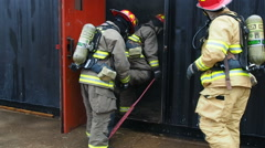 Firefighters entering training center Stock Footage