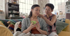 Multi racial girl friends braiding hair smiling using mobile phone hanging out Stock Footage