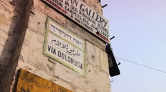 Tilt-down from street sign to the narrow Via Dolorosa in Jerusalem Stock Footage