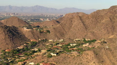 Flight over arid hills hiding pockets of residential areas to reveal Phoenix. - stock footage