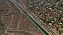 High flight over an Arizona canal with wide view of suburbanized desert Stock Footage