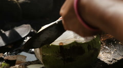 woman opening coconut with big knife - stock footage