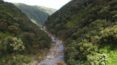 Following a rocky stream on Molokai to orbit plunging waterfalls. Shot in 2010. - stock footage