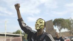 Protester with Golden Anonymous Guy Fawkes Mask and fist up Stock Footage