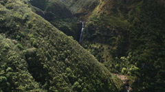 Flight past steep wooded slope to reveal and orbit plunging waterfalls on Stock Footage