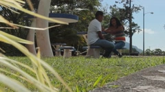 Couple sits at table in park while the wind goes through grass (HD) Stock Footage