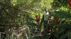 Latino couple walk hand in hand across bridge through tropical garden (HD) Stock Footage