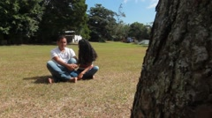Latino couple sitting in grass in tropical park talking (HD) Stock Footage