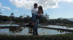 Latino man holds his wife in his arms next to pool in tropical park (HD) Stock Footage