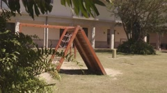 Young boy climbing up rope ladder on playground Stock Footage