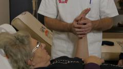 Physiotherapist doing exercises for injured wrist of old female patient, tilt up Stock Footage