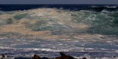 A sandy wave churning and exploding above a rocky reef - stock footage