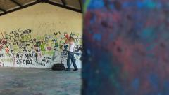 Drunk teen drinking and tripping in building with graffiti walls - stock footage