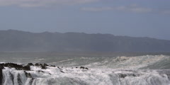 Breaking waves obscuring the Hawaiian coastal hills in the background - stock footage